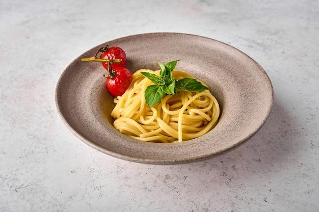 Паста спагетти с запеченными помидорами черри и базиликом на керамической тарелке на светлом фоне крупным планом