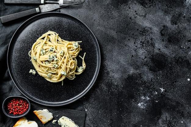 ブルーゴルゴンゾーラチーズソースのスパゲッティパスタ。黒の背景