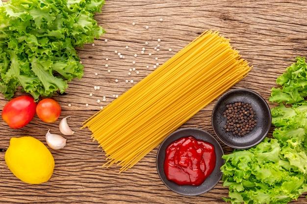 素朴な天然木テクスチャの背景にケチャップ、コショウ、レタス、トマト、ニンニク、レモンのスパゲッティパスタ、料理の材料、上面図