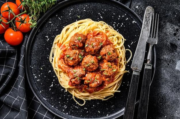 ミートボールとトマトソースのスパゲッティパスタ。イタリア料理。黒の背景。上面図。