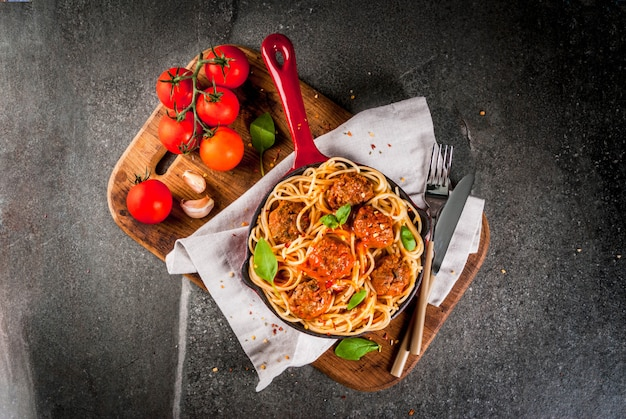 Spaghetti pasta with meatballs, basil tomato sauce in red cast iron pan, on black stone table with cutting board
