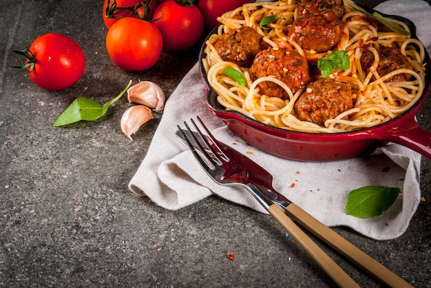 Spaghetti pasta with meatballs, basil tomato sauce in red cast iron pan, on black stone table