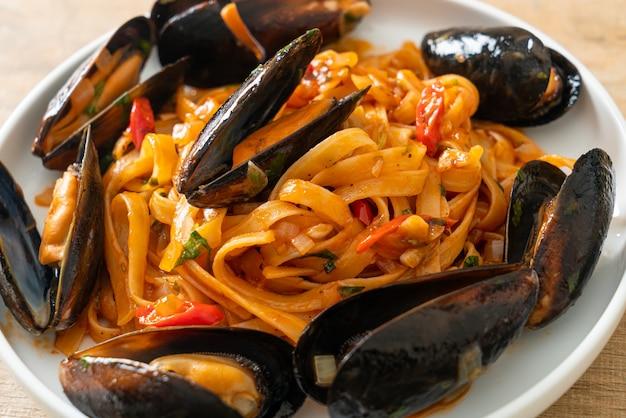 Паста спагетти с мидиями или моллюсками и томатным соусом - итальянская кухня Premium Фотографии