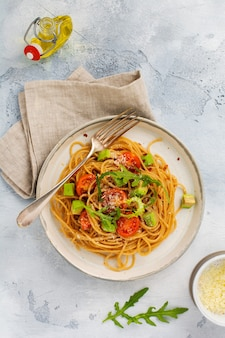 소박한 흰색 접시에 페스토, 아보카도, 토마토를 넣은 스파게티 파스타. 원시 채식주의 음식 개념입니다. 평면도.