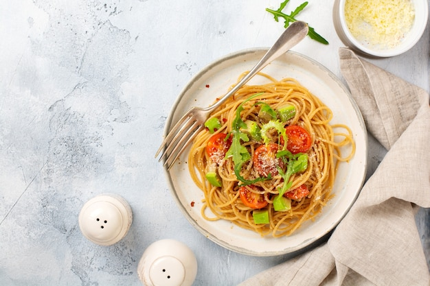 Spaghetti pasta with pesto, avocado and tomatoes in rustic white plate. raw vegan food concept. top view.