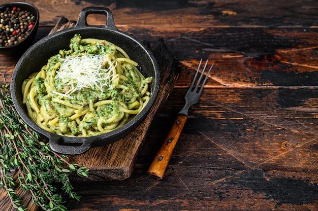 鍋にペストソース、ほうれん草、パルメザンチーズを入れたスパゲッティパスタ。暗い木の背景。上面図。スペースをコピーします。