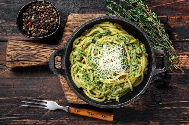 鍋にペストソース、ほうれん草、パルメザンチーズを入れたスパゲッティパスタ。暗い木の背景。上面図。