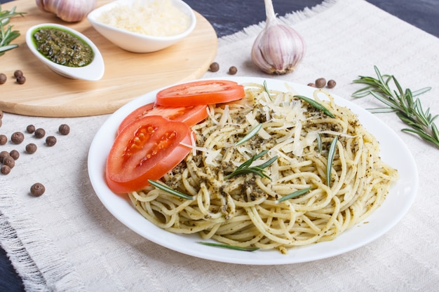 Spaghetti pasta with pesto sauce, tomatoes and cheese on a linen tablecloth on black