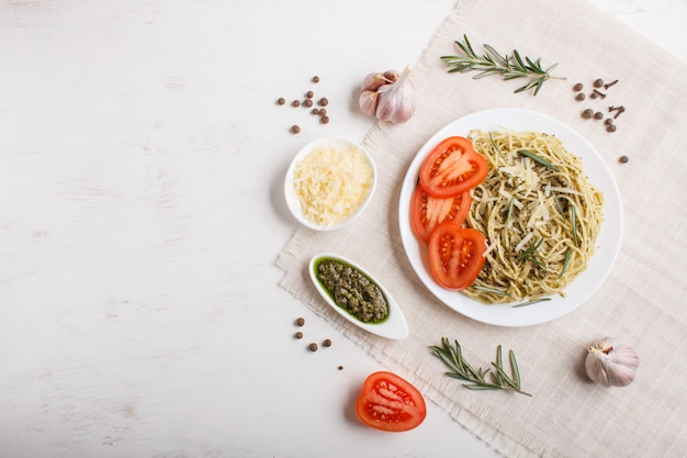 Spaghetti pasta with pesto sauce, tomatoes and cheese on a linen tablecloth on white wooden background.
