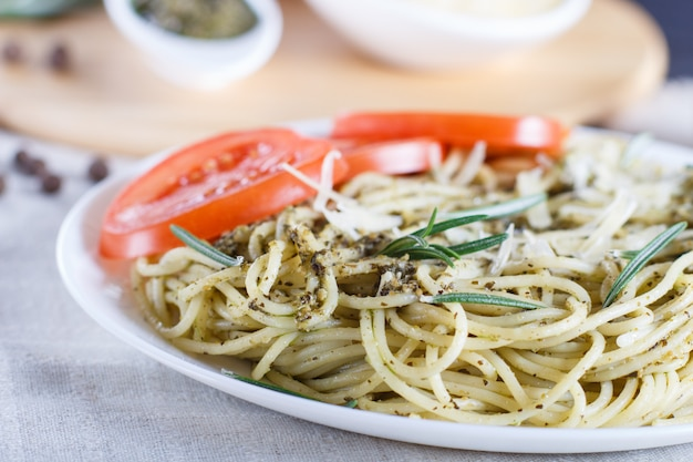 Spaghetti pasta with pesto sauce, tomatoes and cheese on a linen tablecloth.