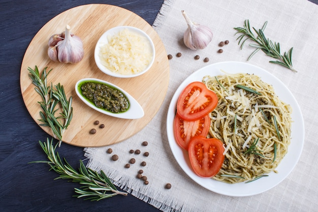 Spaghetti pasta with pesto sauce, tomatoes and cheese on a linen tablecloth