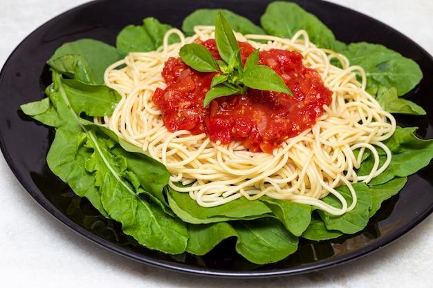 白い大理石の背景と黒いプレートに赤いソースとルッコラのスパゲッティパスタ Premium写真