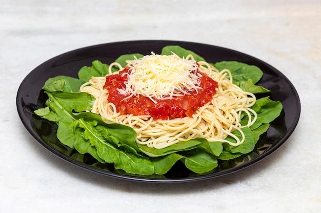 白い大理石の背景と黒いプレートに赤いソース、ルッコラ、パルメザンチーズのスパゲッティパスタ Premium写真