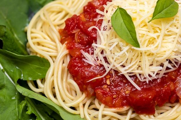 白い大理石の背景と黒いプレートに赤いソース、ルッコラ、パルメザンチーズのスパゲッティパスタ