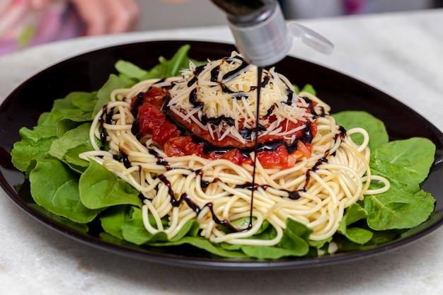 白い大理石の背景の黒いプレートに赤いソース、ルッコラ、パルメザンチーズ、バルサミコ酢のスパゲッティパスタ