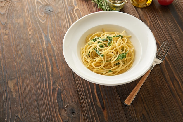 Spaghetti pasta with spinach leaves and cheese on a white plate on wooden table