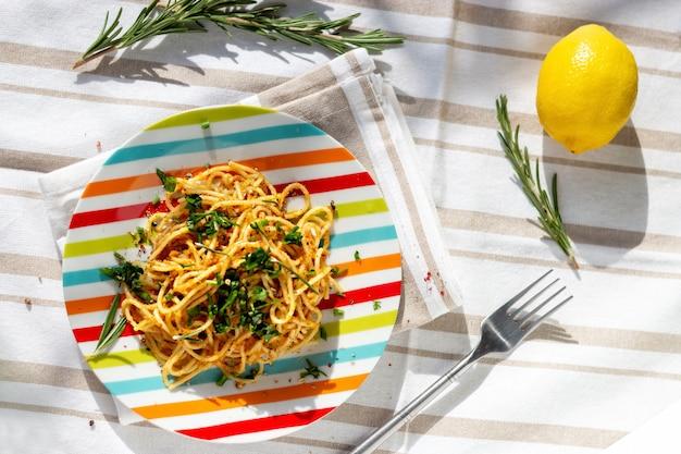 Паста спагетти с поджаренными панировочными сухарями с чесноком, лимоном и розмарином. выборочный фокус. вид сверху.