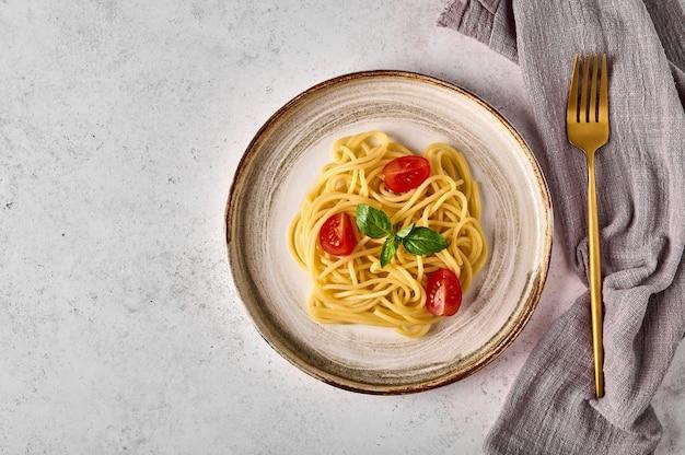 Паста спагетти с томатным черри, пармезаном и базиликом на керамической тарелке с вилкой и салфеткой