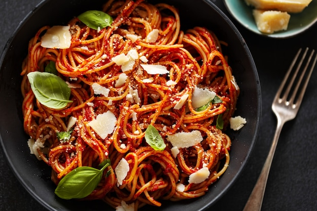 Spaghetti pasta with tomato sauce cheese and basil served in bowl.