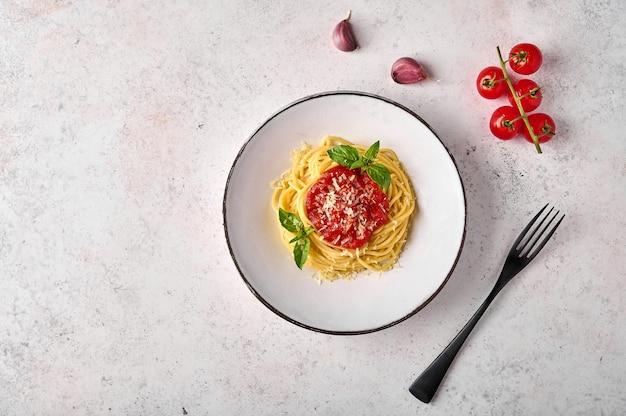 Паста спагетти с томатным соусом, пармезаном и базиликом на белой тарелке с черной вилкой на свете