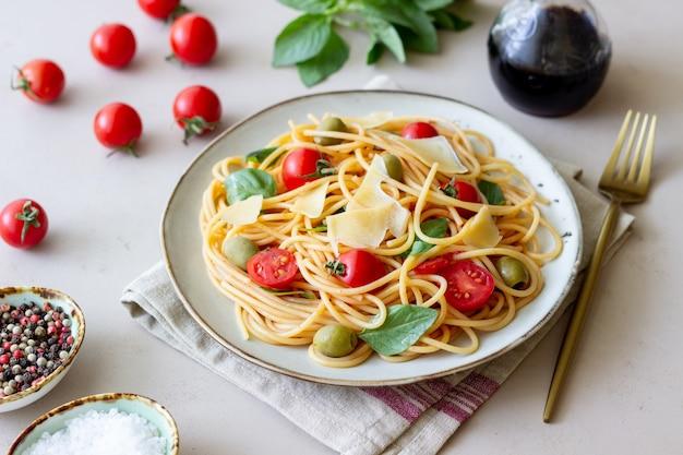 Паста спагетти с помидорами, базиликом, оливками и сыром пармезан. здоровое питание. вегетарианская пища.