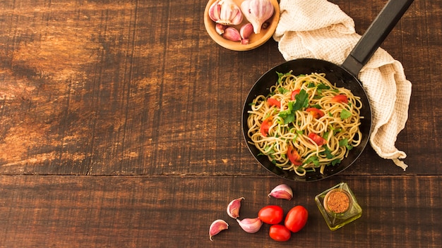 Spaghetti pasta with tomatoes and garlic cloves on wooden backdrop