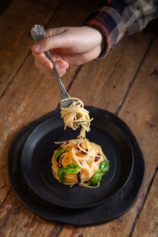 Spaghetti pasta with vegetables, pepper, basil leaves on black round plate on brown rustic vintage wooden background