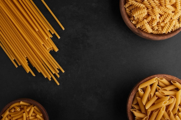 Spaghetti and pastas on black background, top view.
