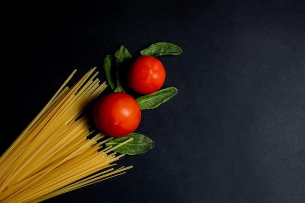 暗い背景の上面で調理するためのスパゲッティペースト、トマト、その他の製品。テキスト用のスペース、上面図