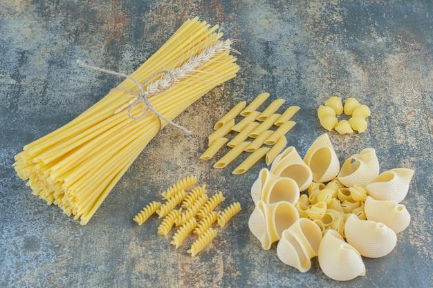 Spaghetti, penne, fusilli e paste di pila, sulla superficie di marmo.