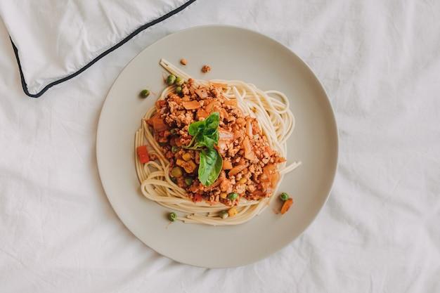 흰 접시에 제공되는 갈은 돼지고기를 곁들인 스파게티 소스