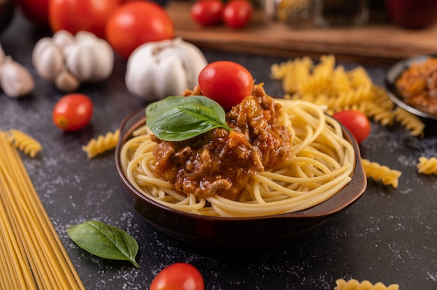 Spaghetti saute in a gray plate with tomatoes and basil