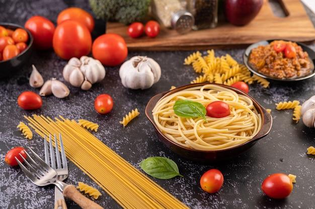 Соте из спагетти в серой тарелке с помидорами и базиликом