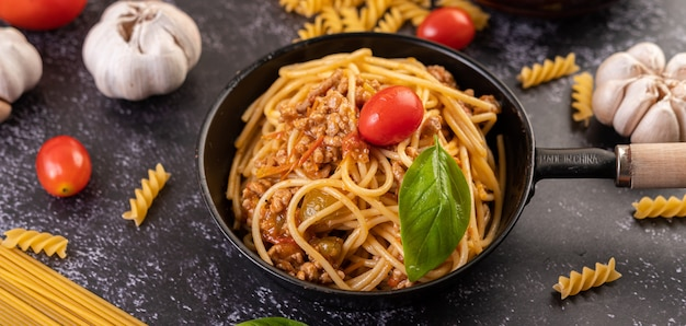 Spaghetti sauteed in a pan-fried with tomatoes and basil
