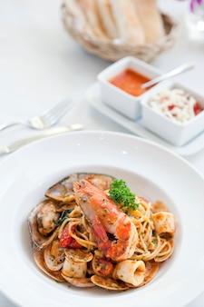 Спагетти с морепродуктами в белой тарелке на столе