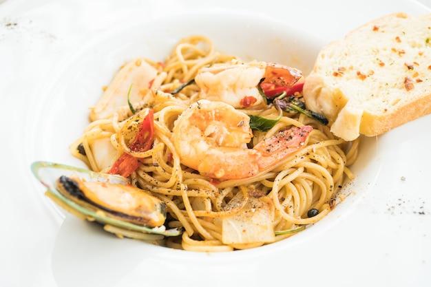 Морепродукты спагетти в белой тарелке