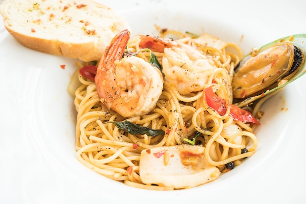Спагетти из морепродуктов в белой тарелке