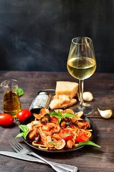 Макароны из морепродуктов спагетти с моллюсками и креветками с мидиями и помидорами на деревянном столе. рецепт итальянской кухни. вид сверху