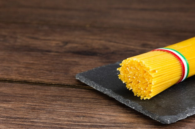 Spaghetti on slate with wooden background