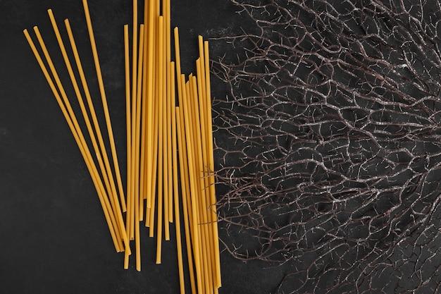Bastoncini di spaghetti su sfondo nero.