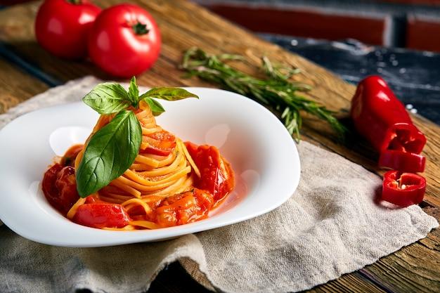 Spaghetti tomatoes basil on wooden background