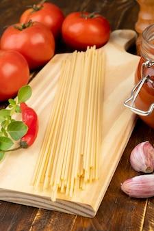 Спагетти, помидоры, чеснок, перец и зелень над деревянным столом.