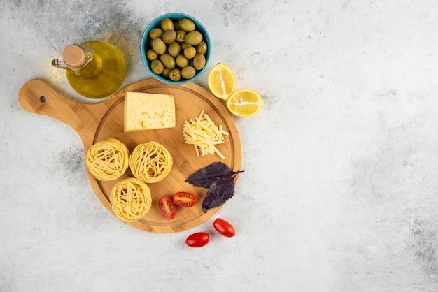 Spaghetti, verdure e formaggio su tavola di legno con olive.