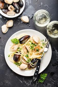 Спагетти вонголе, итальянская паста из морепродуктов с моллюсками и мидиями, в тарелке с травами и двумя стаканами белого вина на деревенском каменном фоне.