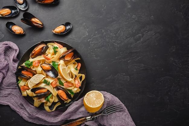 スパゲッティボンゴレ、アサリとムール貝のイタリアンシーフードパスタ、素朴な石の背景にハーブを添えたプレート。伝統的なイタリアの海の料理、クローズアップ、上面図。コピースペース