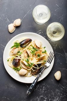 Spaghetti vongole, italian seafood pasta with clams and mussels, in plate with herbs and two glasses of white wine on rustic stone background.