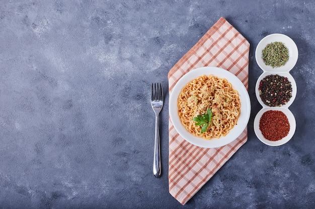 Spaghetti in un piatto bianco con spezie intorno, vista dall'alto.