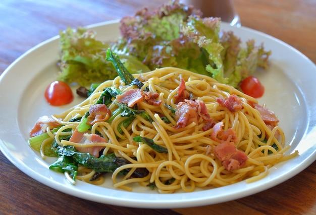 Спагетти с беконом на белой тарелке
