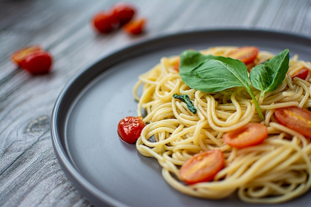 Spaghetti with basil and cherry tomatoes on a wooden background