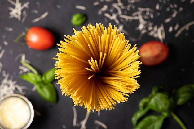 Spaghetti with basil and tomatoes on a black background, top view